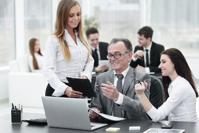 Commercieel team die met het hoofd van financi?le gegevens bespreken stock afbeelding
