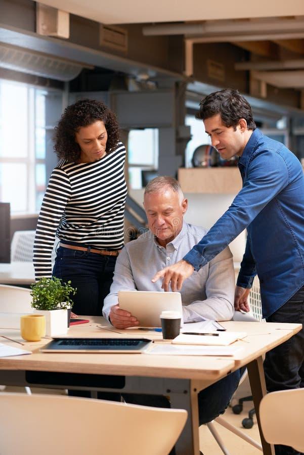 Commercieel team die samen over een tablet in een bureau spreken stock foto