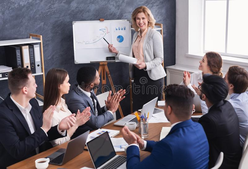 Commercieel team die succesvolle vrouwelijke manager gelukwensen op vergadering royalty-vrije stock foto