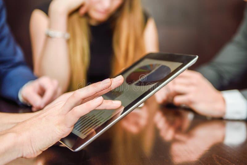 Commercieel team die tabletcomputer met behulp van om met financiële gegevens te werken royalty-vrije stock fotografie
