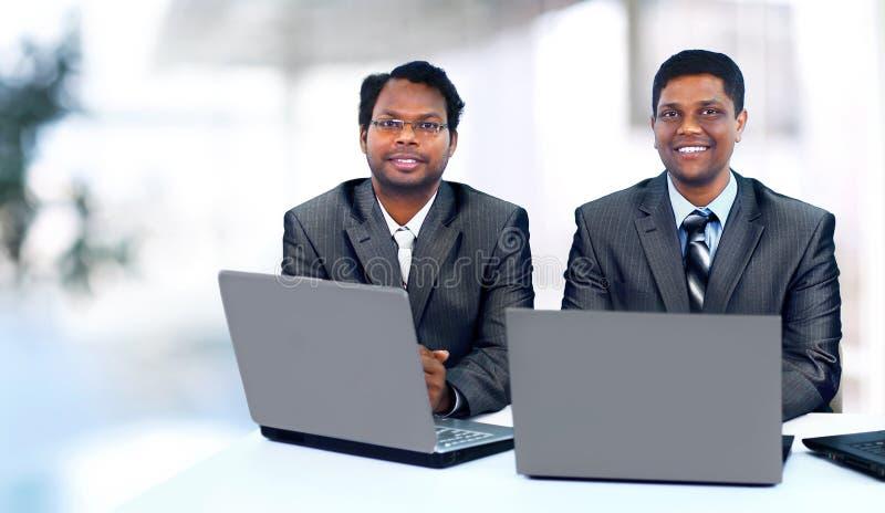 Commercieel team die tussen verschillende rassen bij laptop werken stock afbeeldingen