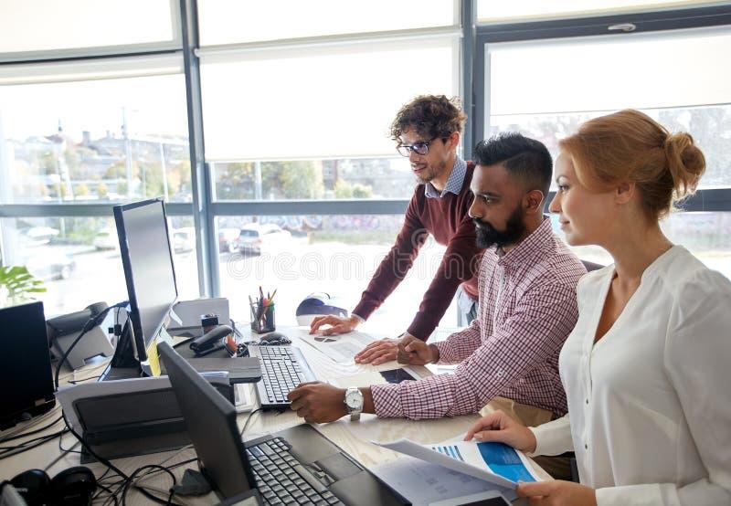 Commercieel team met computers en documenten op kantoor stock foto