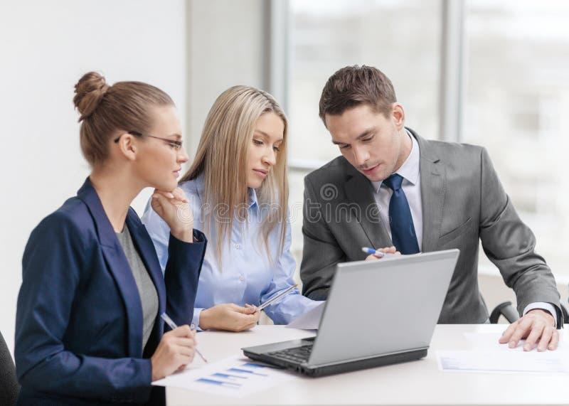Commercieel team met laptop die bespreking hebben stock afbeeldingen