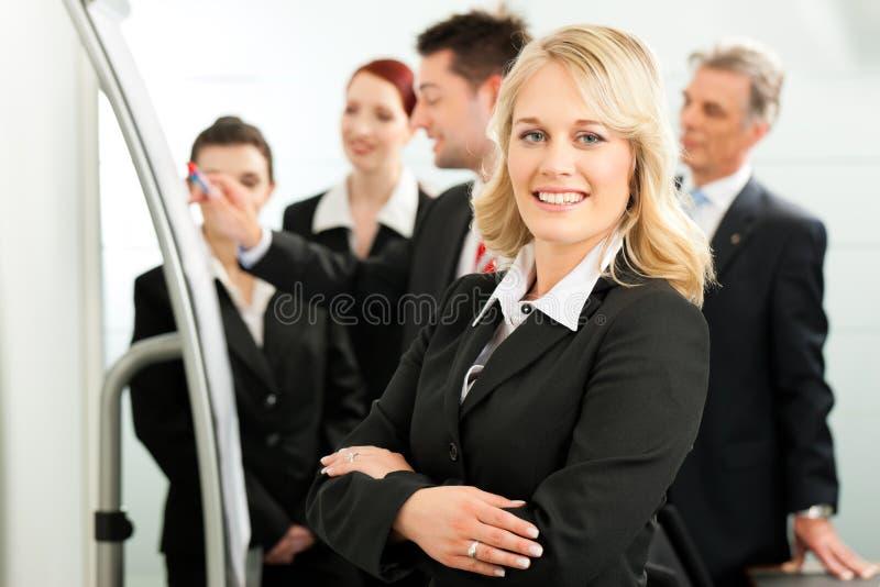 Commercieel Team met leider in bureau stock afbeeldingen