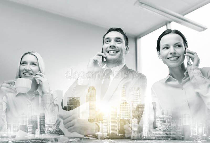 Commercieel team met smartphones die op kantoor werken stock afbeeldingen