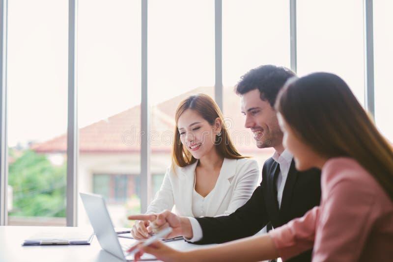 Commercieel team op vergadering die in bureau binnenlandse brainstorming, aan laptop en tabletcomputer werken stock fotografie