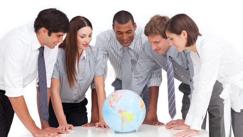 Commercieel team rond een aardse bol stock fotografie