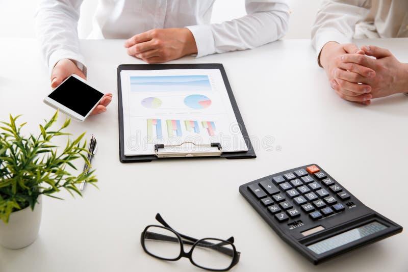 Commercieel team twee collega's die de nieuwe gegevens van de plan financiële grafiek over bureaulijst bespreken stock foto's