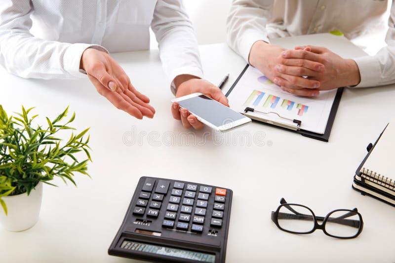Commercieel team twee collega's die de nieuwe gegevens van de plan financiële grafiek over bureaulijst bespreken royalty-vrije stock afbeelding