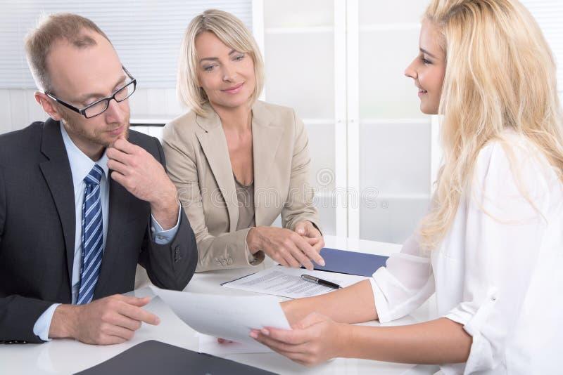 Commercieel team van de mens een vrouwenzitting rond een lijst die tog spreken royalty-vrije stock afbeeldingen