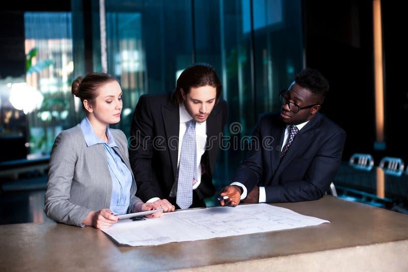 Commercieel team van het herzien drie projectplan stock afbeeldingen