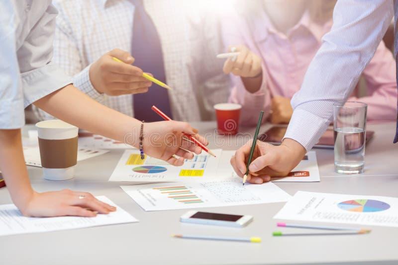 Commercieel Teamvoorzien van een netwerk - bureaulijst met Grafieken en Mensenhanden stock afbeeldingen