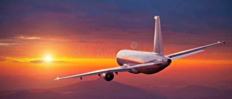 Commercieel vliegtuig die boven bergen in zonsondergang vliegen royalty-vrije stock afbeeldingen