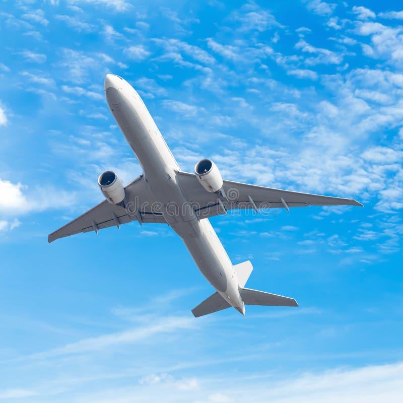 Commercieel vliegtuig die met blauwe hemelachtergrond vliegen met klem royalty-vrije stock foto