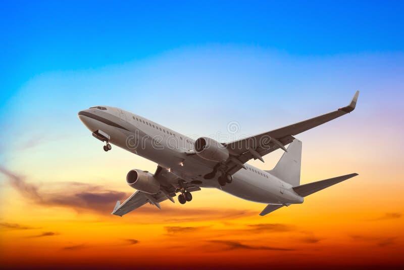 Commercieel vliegtuig die met mooie zonsondergang vliegen stock afbeelding