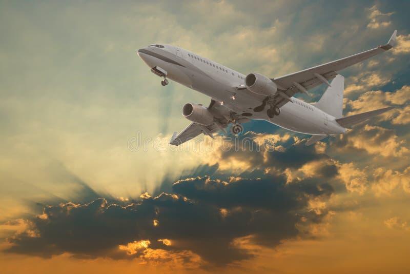 Commercieel vliegtuig die met wolken en zonstralen vliegen royalty-vrije stock afbeeldingen