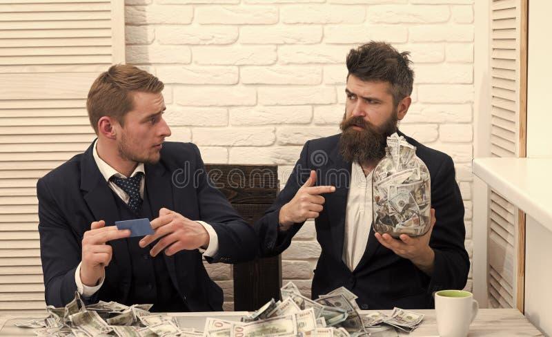 Commercio e finanze Soci commerciali, uomini d'affari alla riunione nell'ufficio Il capo barbuto giudica il barattolo pieno di co fotografia stock