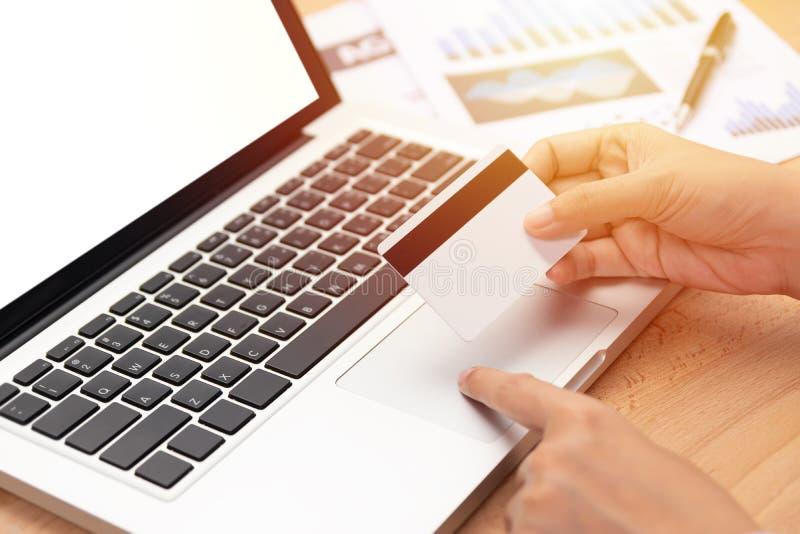 Commercio elettronico e concetto online di compera donna che giudica una carta di credito e un acquisto che effettuano pagamento  fotografia stock