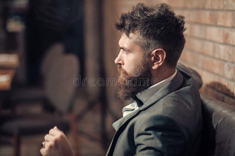 Commercio sul andare Il cliente sicuro della barra si siede in caffè Uomo d'affari con la barba lunga nel club del sigaro Riunion immagini stock