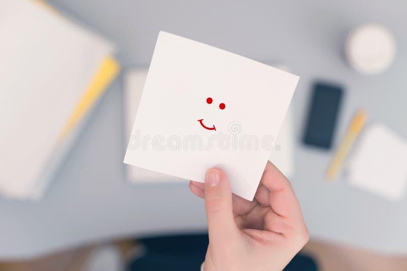 Commis de femme dans le bureau tenant l'autocollant de papier avec l'icône positive de sourire photos libres de droits