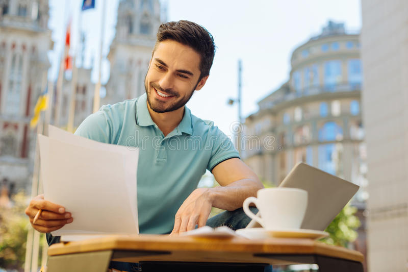 Committed handsome man reading the documents carefully royalty free stock images