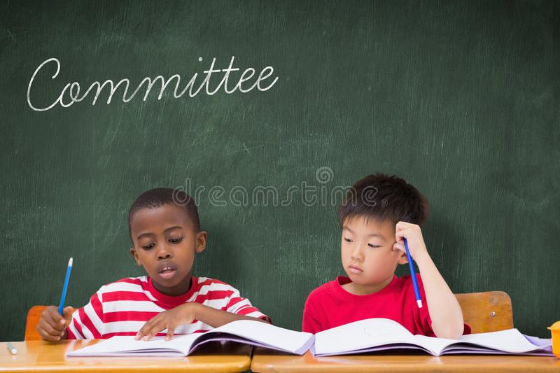 Committee against green chalkboard. The word committee and cute pupils writing at desk in classroom against green chalkboard stock photo