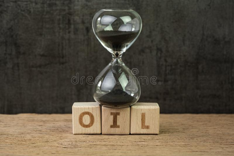 Commodity, oil price countdown for up and down, hourglass or sandglass on wooden cube block with alphabet building the word Oil on. Wood table, dark black royalty free stock image