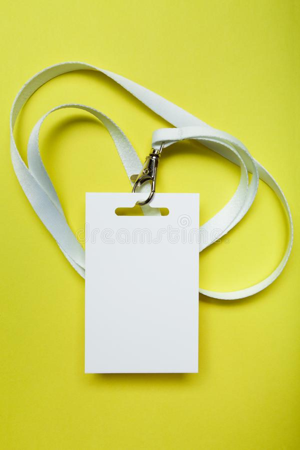 A common blank label name tag hanging on the neck with a red thread. Empty layout isolated on yellow stock images