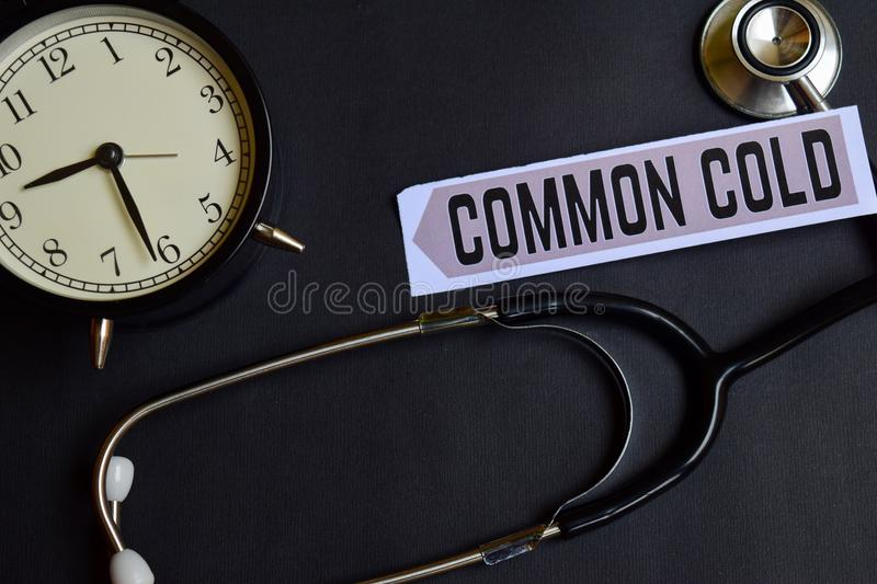 Common Cold on the paper with Healthcare Concept Inspiration. alarm clock, Black stethoscope. royalty free stock image