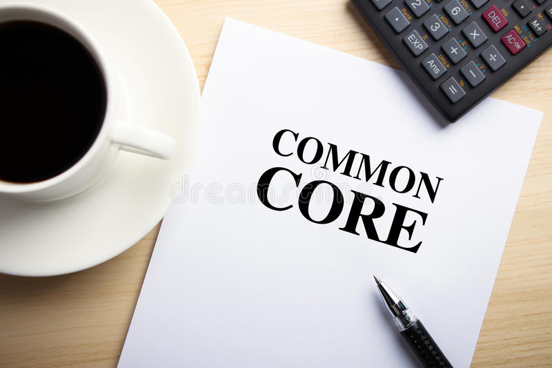 Common Core. Text Common Core is on the white paper with coffee, calculator and ball pen aside stock photos