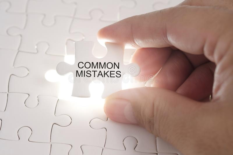 COMMON MISTAKES word on jigsaw puzzle. Businessman hands holding royalty free stock photos