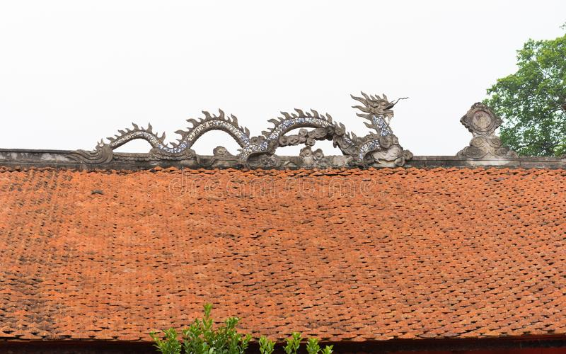Common stone dragon on top of temple roof in Vietnam royalty free stock photo