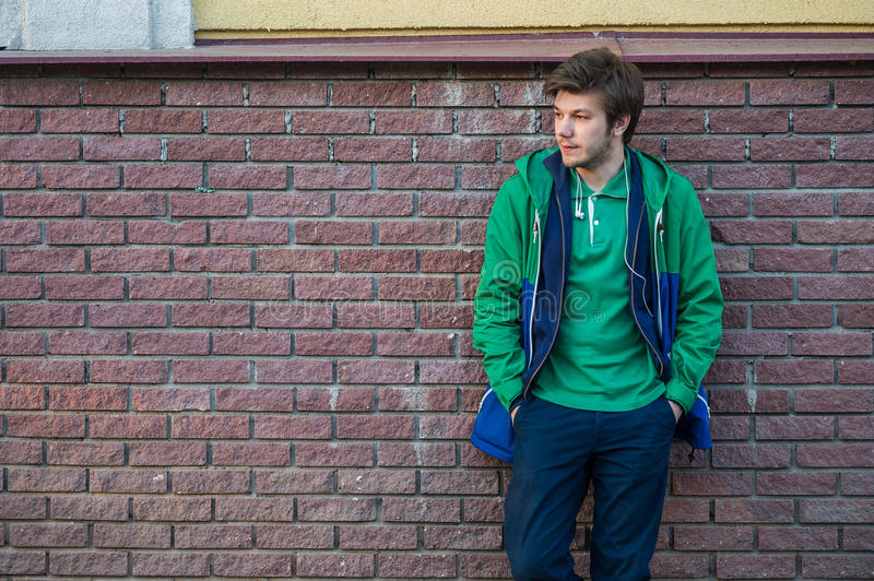 Common young man wearing green t-shirt jacket and jeans against a red brick wall looking sideways stock photography