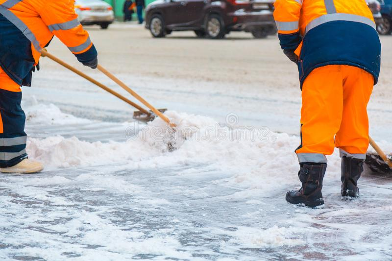 Communal services workers sweep snow from road in winter, Cleaning city streets and roads after snow storm. Moscow, Russia.  stock photo