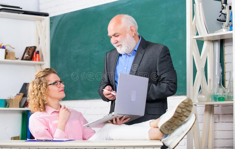 Communicate clearly and effectively. Man mature school teacher and carefree girl student with laptop. High school. College university. Modern school. Teaching royalty free stock images