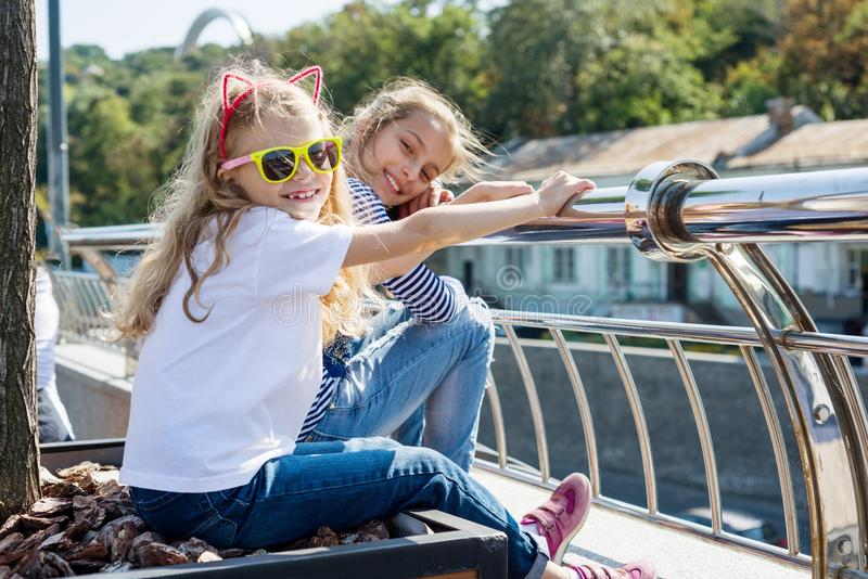 Communicate and relax two girls` children. Urban background. Communicate and relax two girls` children. wo pretty little girls are looking at the camera and royalty free stock photos