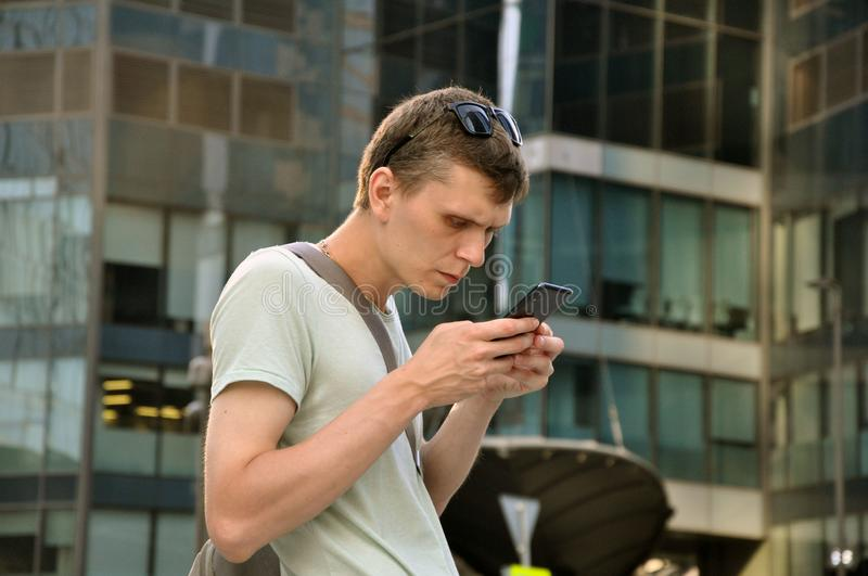 Communicates in the messenger on a smartphone, on the go in the city center stock photos