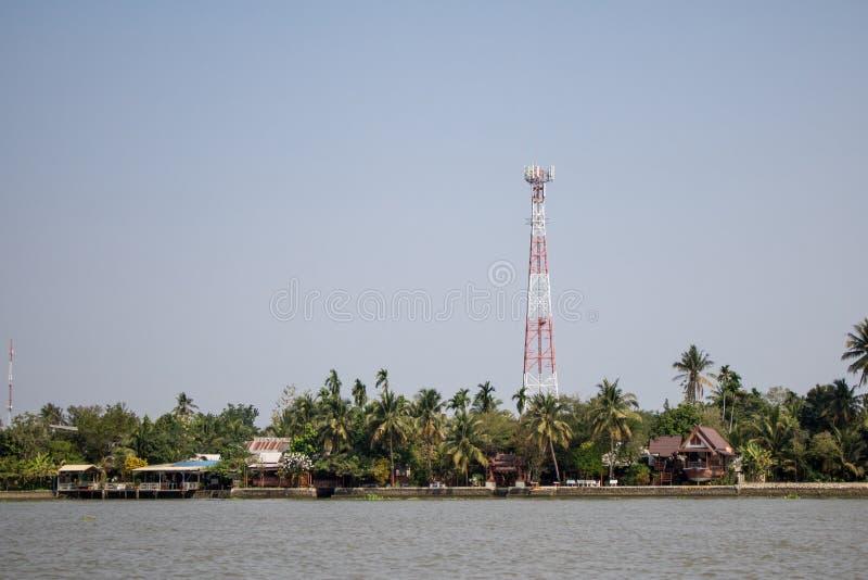 Communicatie toren in een dorp dichtbij de rivier met de blauwe achtergrond van de Wolkenhemel stock afbeelding