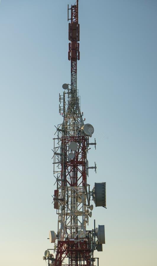 Communicatie toren met antennes tegen blauwe hemel stock afbeeldingen