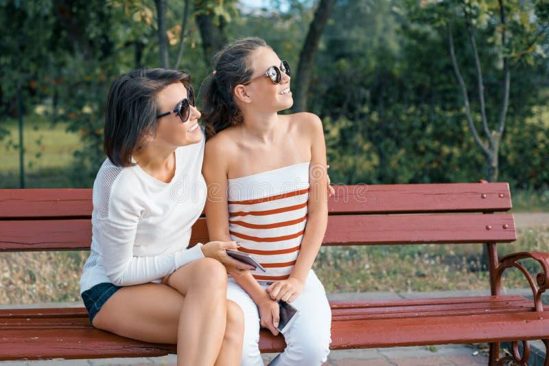 Communicatie tussen ouder en kind Mamma en dochter en tiener die terwijl het zitten op de bank in het park spreken lachen royalty-vrije stock afbeeldingen