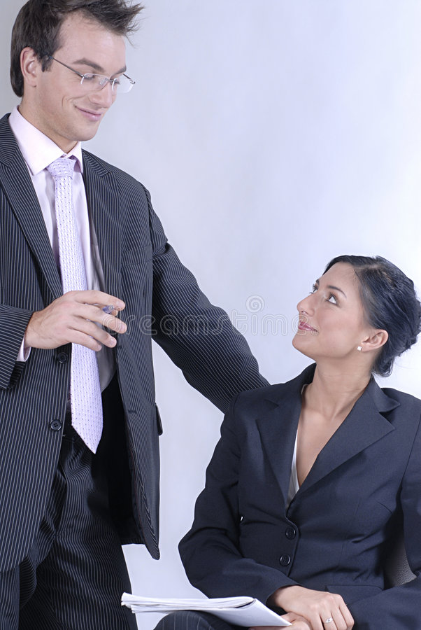 Communicating business. Picture of standing standing man business reading notes and woman sitting on chair and holding notes and pen, both business dressed stock images