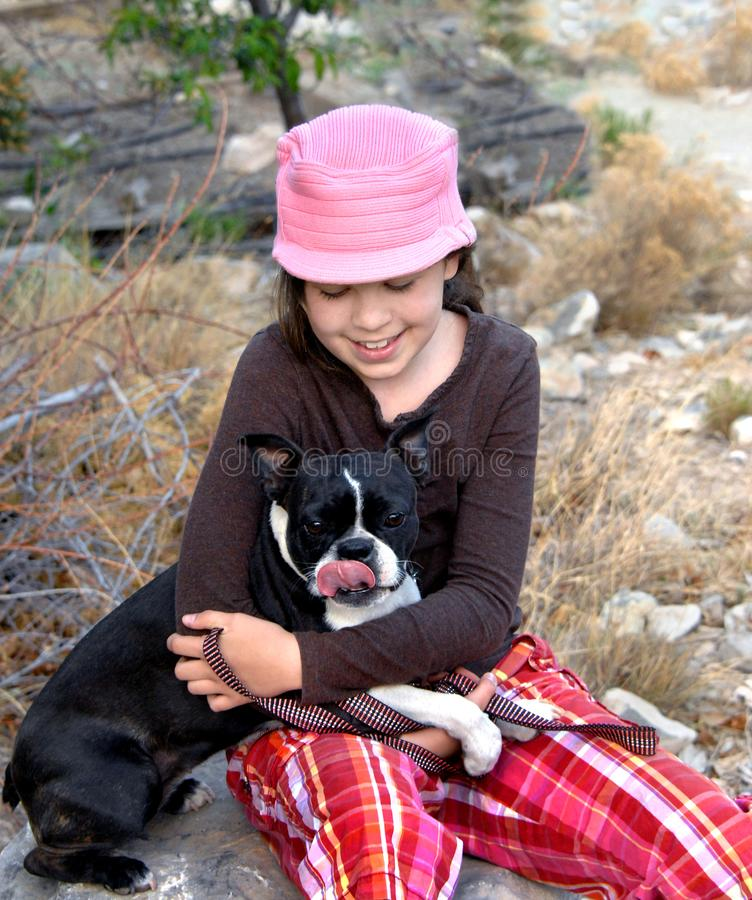 Communicating With Her Dog. Young girl enjoys hiking with her dog. She sits down and is talking to her dog. Dog has tongue out licking his mouth. Girl has on stock photo