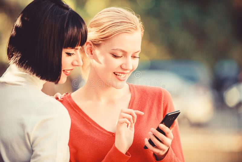 Communicating online. Girls communicating looking at phone. Buy online. Two women with smartphone communicating outdoors. Social networks concept. Sharing link stock image
