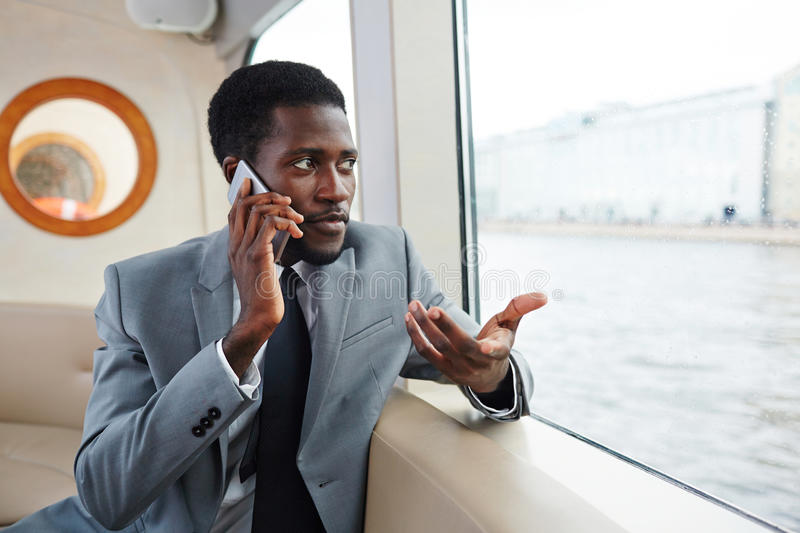 Communicating by smartphone. Confident banker or rich man speaking by smartphone while traveling by steamship royalty free stock images
