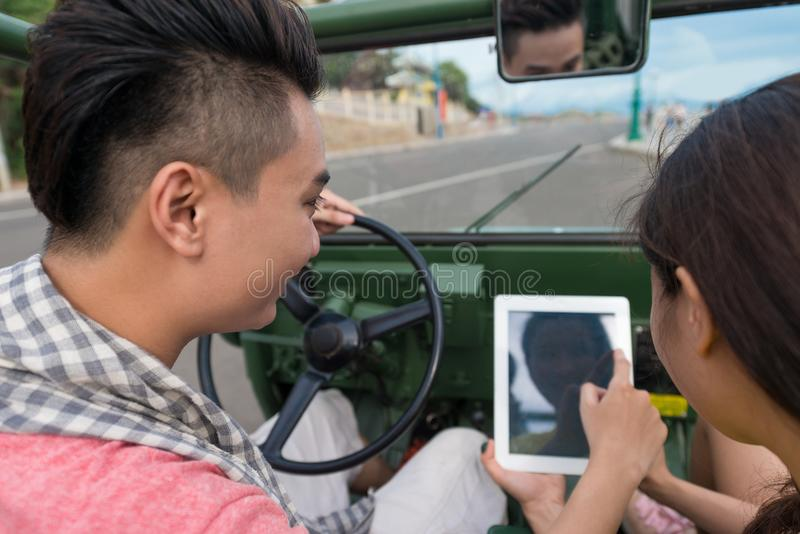 Communicating by tablet. Young couple communicating by touchpad while driving a car royalty free stock images