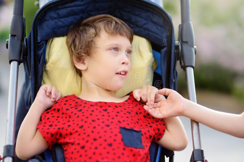 Communication of boy and a disabled girl in a wheelchair walking in the Park summer. Inclusion. Child cerebral palsy. Family with disabled kid royalty free stock photo