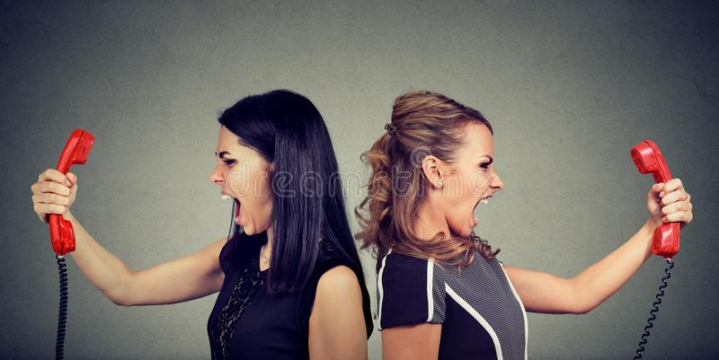 Communication concept. Two angry women screaming at each other over the phone royalty free stock photo