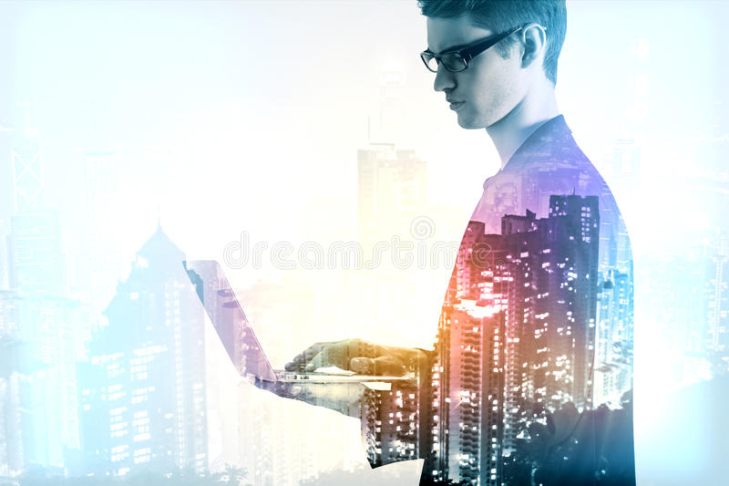Communication concept. Young businessman using laptop on night city background. Communication concept. Double exposure stock photo