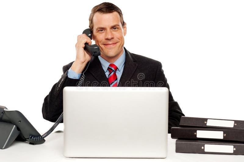 Communication exécutive mâle avec le client photographie stock