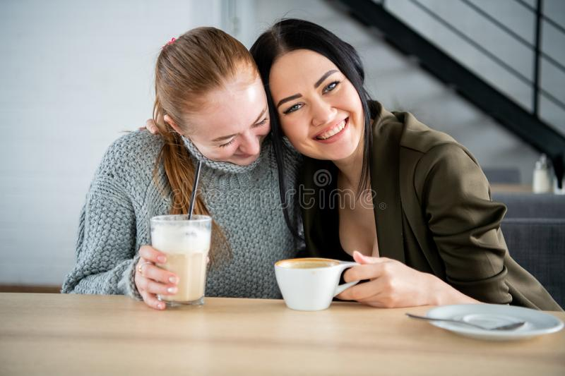 Communication and friendship concept - smiling young women with coffee cups at cafe royalty free stock image